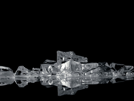 ice fantasy - pile of different bright ice cubes on reflection surface on  black background photo