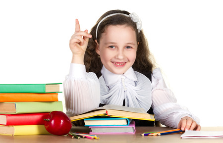 toothless: smiling toothless girl in beautiful  uniform sitting at the table with school accessories and red apple, holding finger up and look at camera on white background  Stock Photo