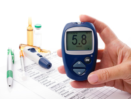 glucometer in womans hand, displlay of glucometer showing  number 5.8, on white background arranging medical form, pen, diabetic syringe and ampoules with drugs