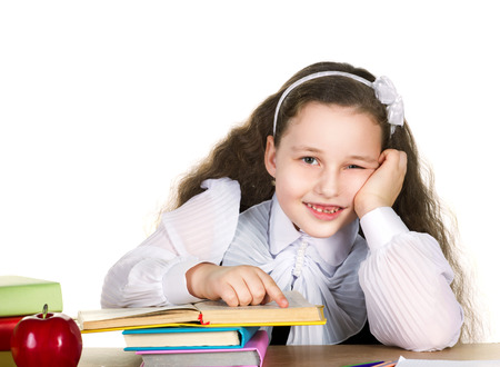 smiling school girl with long curl in white blouse sit at the table prop up hand her head, on that lie many colorful books, pencils and red beautiful apple on white background  photo
