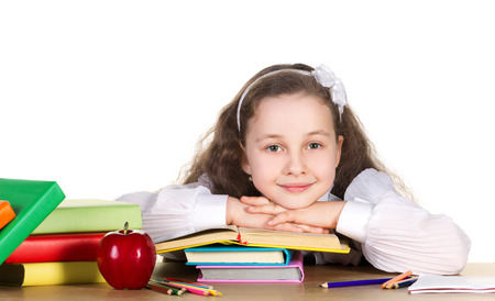 smiling school girl with long curl in white blouse sit at the table, on that lie many colorful books, pencils and red beautiful apple on white background  photo