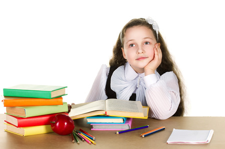 pensive schoolgirl with long curl in white blouse sit at the table prop up hand her head, on that lie many colorful books, pencils and red beautiful apple on white background  photo