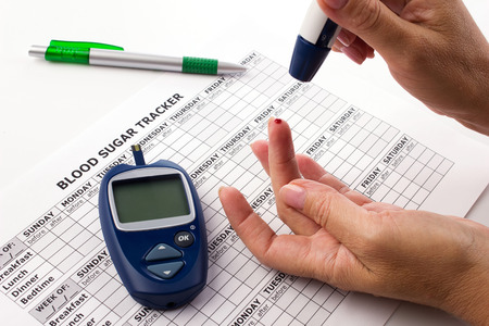 woman doing a test for determination  level sugar in blood, near lie glucometer, medicine form for control measurement and pen on white background