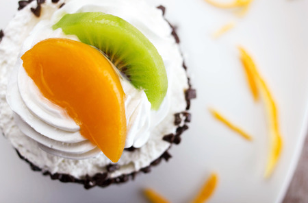 close-up cake with cream and slices of orange and lime on white plate, top view photo