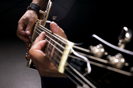 fretboard: musician playing on guitar, close-up shot