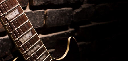 closeup of guitar on dark brown brick wall background