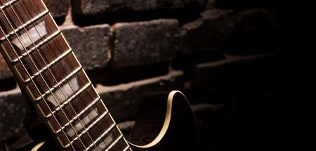 closeup of guitar on dark brown brick wall background photo