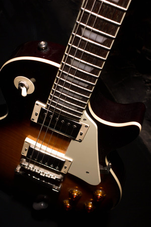 tremble: sunburst electric guitar close-up view in the dark