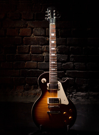 tremble: electric guitar staying near brick wall
