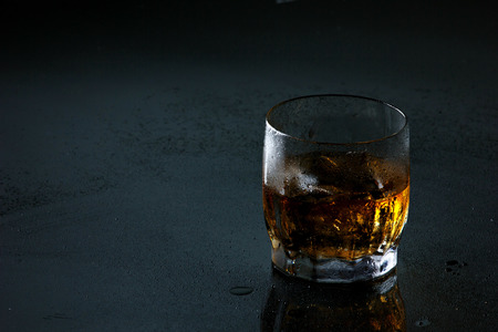 misted: translucent brown-gold drink with ice cubes in glass on misted dark grey surface  with place for your text