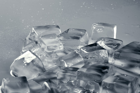 misted: pile of different ice cubes on reflection table with water drop, on misted light grey surface