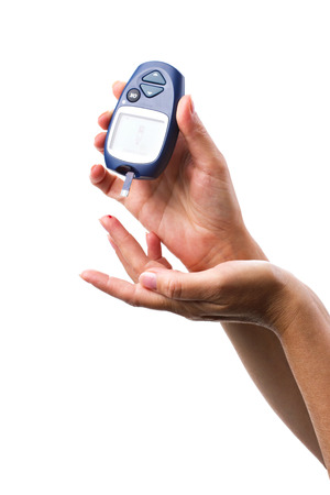 blood sugar: glucometer in womans hand on a white background