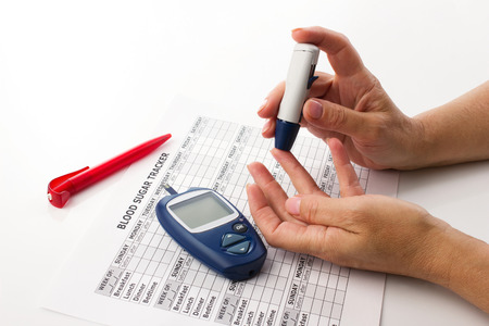 elderly womans hands doing a test for determination  level sugar in blood near lie glucometer, medicine form and pen on white background