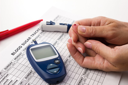 womans hands doing a test for determination  level sugar in blood near lie glucometer, medicine form and pen on white background