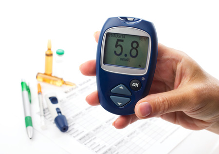 glucometer in womans  hand, displlay of glucometer showing  number 5.8, on white background unfocused  lie medical form, pen, diabetic syringe and ampoules with drugs photo