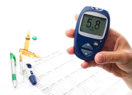 close up glucometer in womans  hand, displlay of glucometer showing  number 5.8, on white  background  lie medical form, pen, diabetic syringe and ampoules with drugs photo
