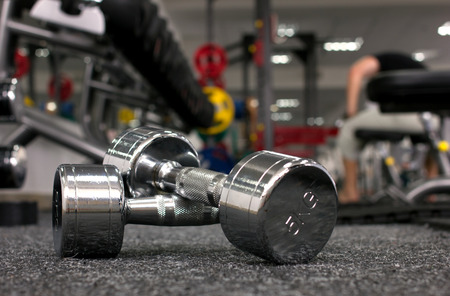 heaviness: Two dumbbells in gymnasium on blurred background