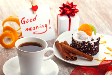 love design - morning coffee in white cup, note with wish good morning, little red heart, gift box, beautiful cup-cake with cinnamon stick on white plate, old wooden surface