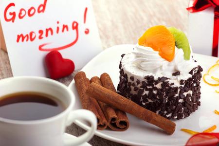 plato del buen comer: diseño del amor - hermoso pastel con canela en un plato blanco, café en la taza blanca, cuenta con deseo buenos días, poco corazón rojo, caja de regalo Foto de archivo