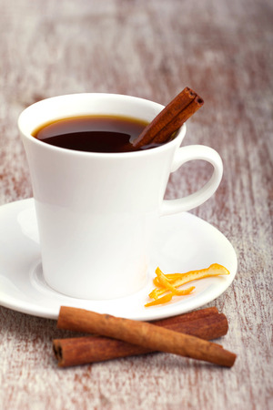 orange peel: white cup with coffee  and cinnamon sticks and orange skin,  old wooden surface Stock Photo