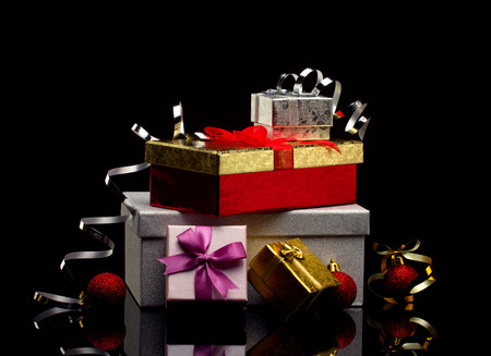 several glamour  gift boxes with bows and bright red balls on dark reflection  background photo