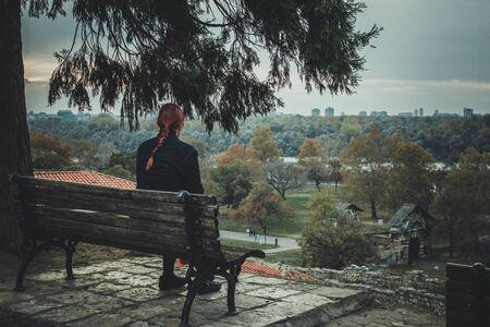 young woman sitting on bench in park, Kalemegdan, Belgrade, Serbia