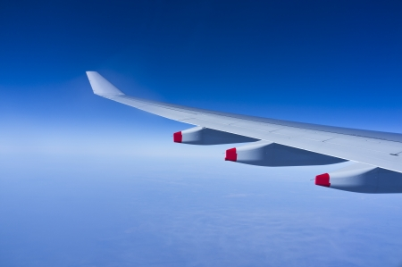 long haul journey: Airplane wing over blue skies and clouds Stock Photo