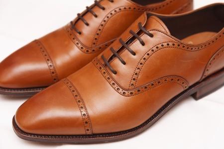 brogues: A pair of tan coloured quarter brogue captoe leather shoes