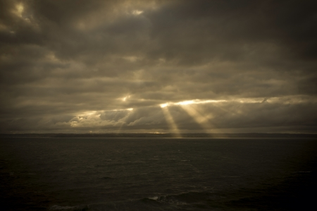 glow: Sun rays piercing through thick clouds at sea
