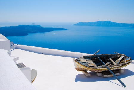 An abandoned boat overlooks the mediterranean sea in Santorini, Greek Islands Zdjęcie Seryjne