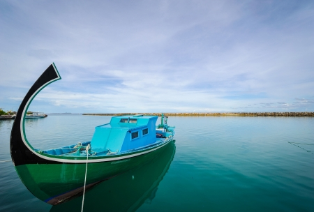 A traditional fishing boat is anchored at an island in the Maldives