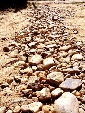The rock trail or gravel stone way on the ground sand go straight to the big gate.