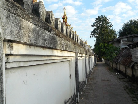 Thais traditional, the ancient wall of temple next to the old walk way street in rural.