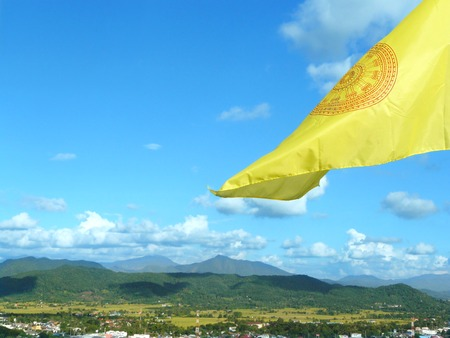Dhamma flag flying in the air into the sky haven  above than mountain. Stock Photo