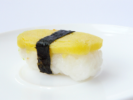 Japanese food. Sushi sweet egg roll with seaweed on white plate, side view isolated on white background. Stock Photo