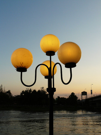 archways: Street lamp shining up in the evening when sunset at the river. Stock Photo