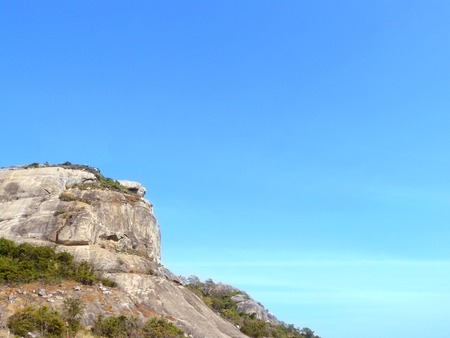 One side the cliff of Chopstick Mountain (KaoTao or KaoTakiap, Hua Hin, Thailand.) with beautiful blue sky a sunny day. Stock Photo