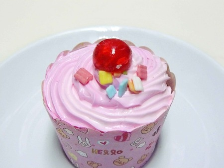 Princess Pink cupcake. The cute cupcake decorated with pink creamy, colorful sweet sugar and red jelly ball on the the top in a white plate. Isolated on white background.