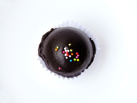 Close Up of chocolate ball with colorful sugar topping in paper cup and white plate isolated on white background.