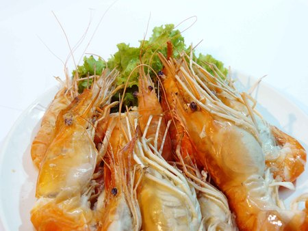 Close up steamed giant river prawns or giant malaysian prawn (Macrobrachium rosenbergii)in a plate Isolated on white background Stock Photo