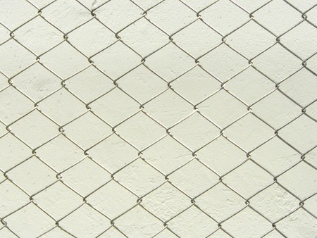 Repeating chain link fence white metal wire mesh or metal net repeats left, right, up and down. The wire mesh fence close up pattern for background and texture.