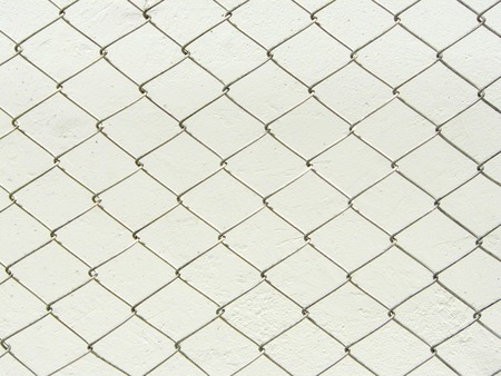 Repeating chain link fence white metal wire mesh or metal net repeats left, right, up and down. The wire mesh fence close up pattern for background and texture isolate on white background. Stock Photo