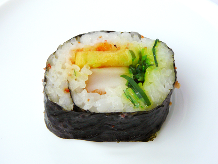 Japanese food. Close up side view of Seaweed sushi roll with sweet egg, flying fish roe and crab stick isolated on white background.