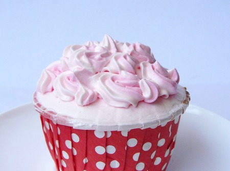 Pink Vanilla cupcake. Vanilla cake in paper cup decorated with white and pink creamy, close up side view on a white plate. Isolated on white background.