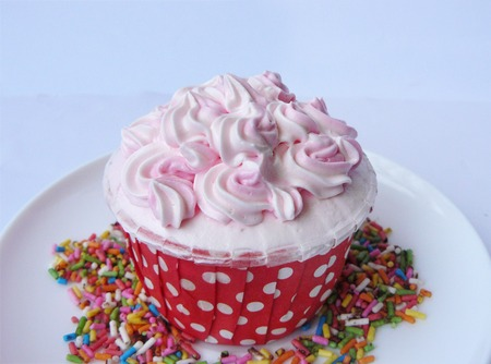 Pink Vanilla cupcake. Vanilla cake in paper cup decorated with white,pink creamy and colorful sugar on a white plate. Isolated on white background.