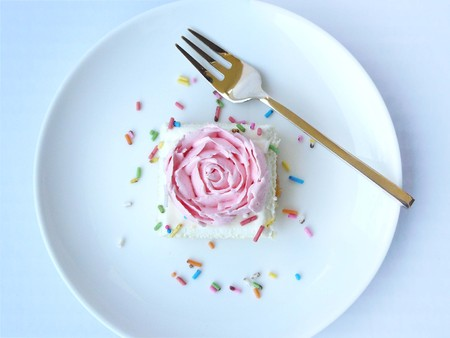 pound cake: Pink rose vanilla cream cake. The vanilla cake decorated with cream of pink rose and sugar color. Close up front view with pinchbeck fork in white plate isolated on background. Stock Photo
