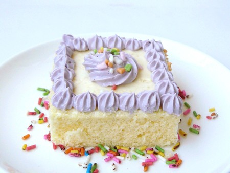 Violet vanilla cream cake. The vanilla cake decorated with violet soft cream, sugar color with stainless fork. Close up front view isolated on white background.
