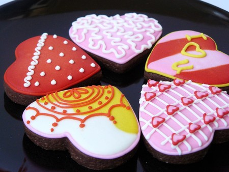 Colorful Love Heart Cookies, The chocolate cookies decorated heart shape with sugar color, close up in black plate isolated on white background.