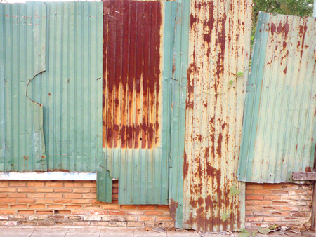 Old green zinc wall and rusty zinc wall on red brick fence for background and texture.