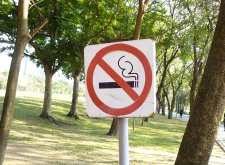 No smoking sign at the public park with green garden as a backdrop in a sunny day.